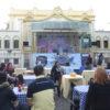 Praça do Coreto, com banda se apresentando no palco, e pessoas sentadas nas mesas comendo