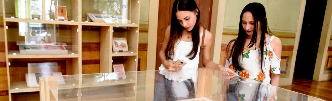 Duas mulheres olham com atenção para instalação de uma exposição, protegida por edoma de vidro, com prateleira com acervos de exposição ao fundo