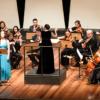 Palco de teatro iluminado, com músicos em performance, e duas mulheres em pé, uma regendo e a outra cantando