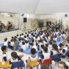 Crianças sentadas no chão e em cadeiras, assistindo a um grupo de músicos